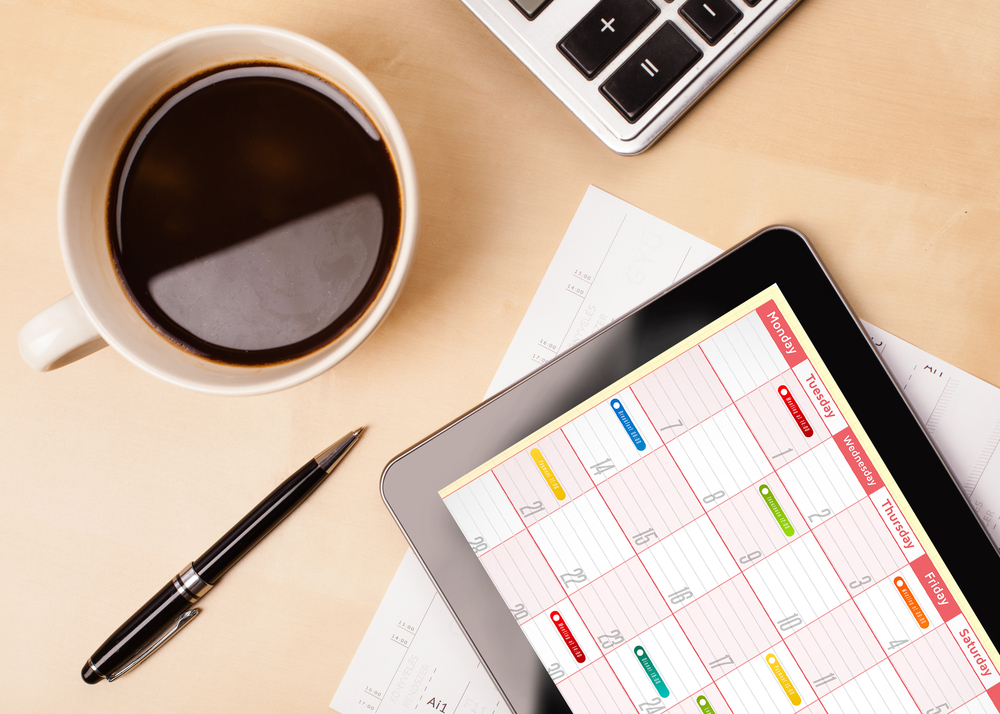 Workplace with tablet showing calendar and a cup of coffee on a wooden work table